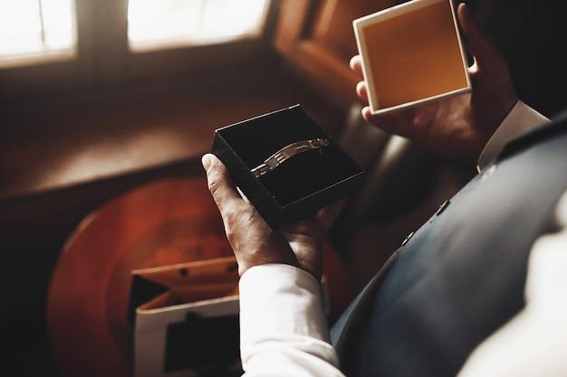 L'homme tient une boîte avec un bracelet et se tient devant une fenêtre dans une pièce sombre