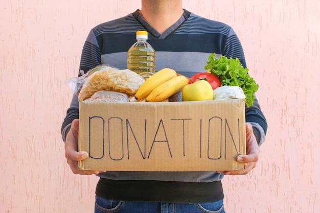 L'homme tient une boîte de dons avec un fond de béton rose clair