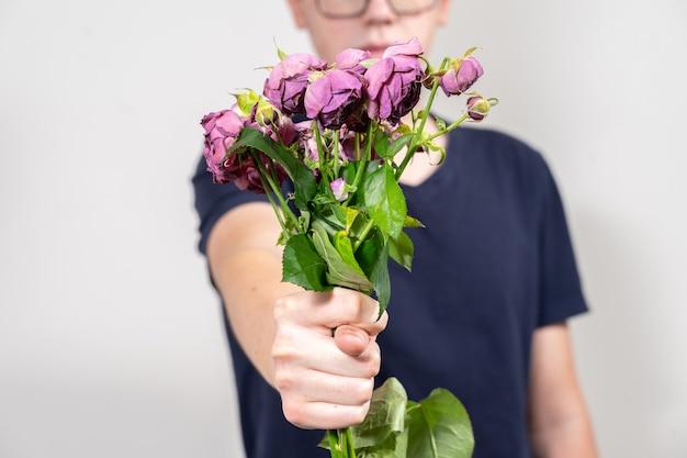 L'homme tient un bouquet de fleurs mortes et fanées et montre la figure