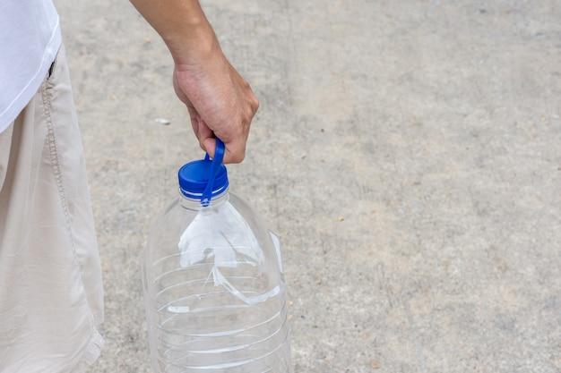 L'homme tient une bouteille en plastique d'eau