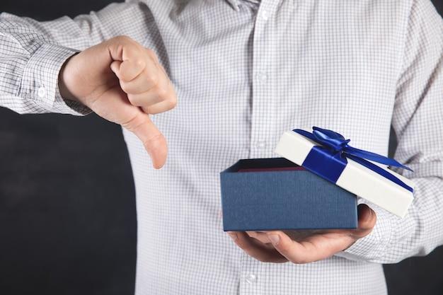Un homme tient un cadeau dans sa main et montre un mauvais signe