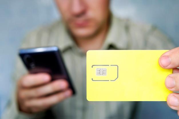 L'homme tient une carte sim jaune et un téléphone portable à la main. espace libre pour la conception et le texte