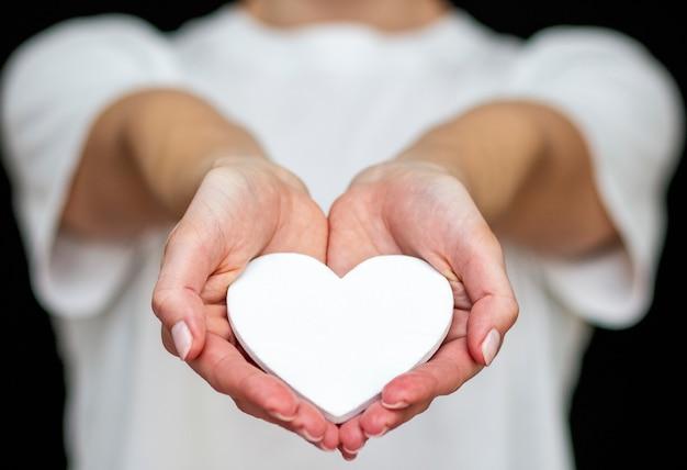 Homme tient coeur blanc dans ses mains sur le fond de vêtements légers