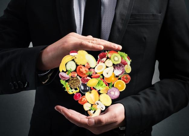 L'homme tient un cœur de légumes et de fruits. une alimentation saine pour le concept de bien-être