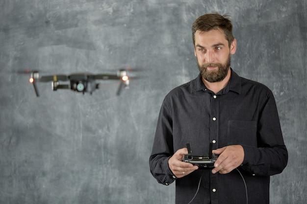 Un homme tient le contrôleur radio d'un quadcopter télécommandé