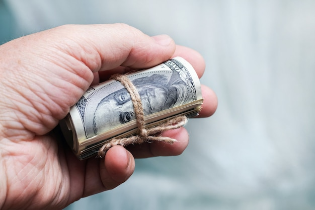 Un homme tient dans sa main de l'argent (dollars américains) dans un rouleau attaché avec une corde