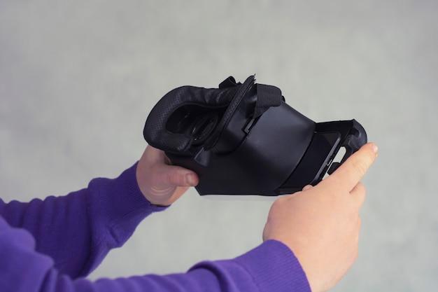 L'homme tient dans ses mains des lunettes pour la réalité virtuelle et la vidéo à 360 degrés. casque vr avec smartphone sur fond clair.