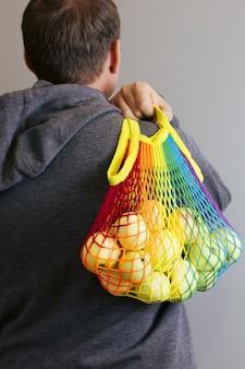Un homme tient dans ses mains un sac à provisions en coton réutilisable, un arc-en-ciel lgbt multicolore avec des pommes vertes à l'intérieur. sur fond gris. concept zéro déchet