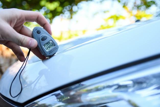 Un homme tient un dispositif pour mesurer l'épaisseur du revêtement avant de polir la voiture. revêtement de peinture avec jauge. concept automobile polonais