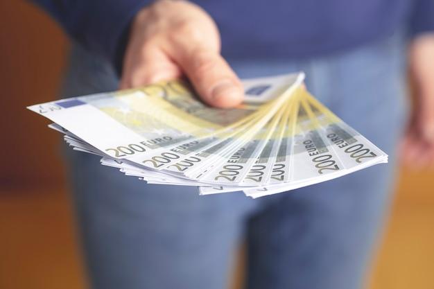 Un homme tient des euros en espèces dans sa main.