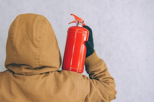 Un homme tient un extincteur rouge dans ses mains sur un fond blanc.