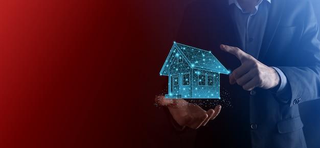 L'homme tient un faible polygone. concept immobilier, homme d'affaires tenant une icône de la maison. maison à portée de main. concept d'assurance et de sécurité de propriété. geste protecteur de l'homme et symbole de la maison