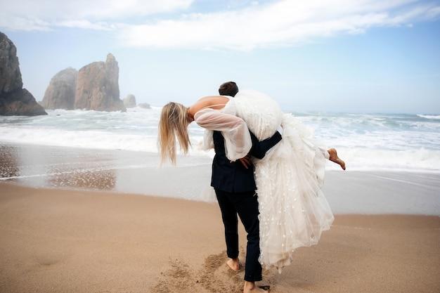 L'homme tient la femme sur son épaule et ils sont sur la plage de l'océan