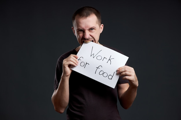 L'homme tient une feuille de papier affiche dans ses mains avec l'inscription je travaille pour la nourriture.