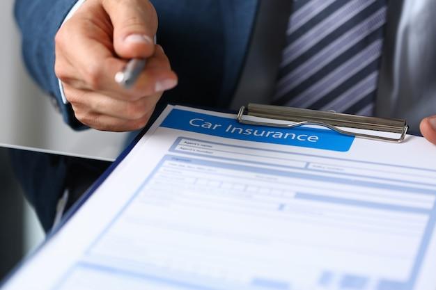 L'homme tient un formulaire de réclamation d'assurance automobile