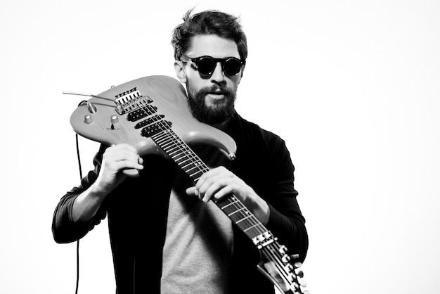 Un homme tient une guitare dans ses mains veste en cuir noir lunettes noires performance musique lumière mur.