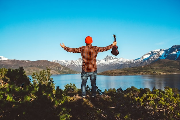 L'homme tient une guitare sur fond de forêts de montagnes et de lacs vêtus d'une chemise