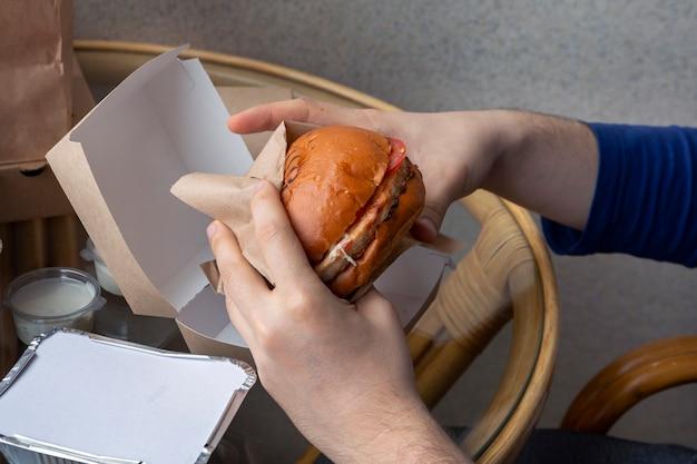 Un homme tient un hamburger dans ses mains assis à une table d'un café de la rue fast food régime malsain excès de graisse dans l'alimentation