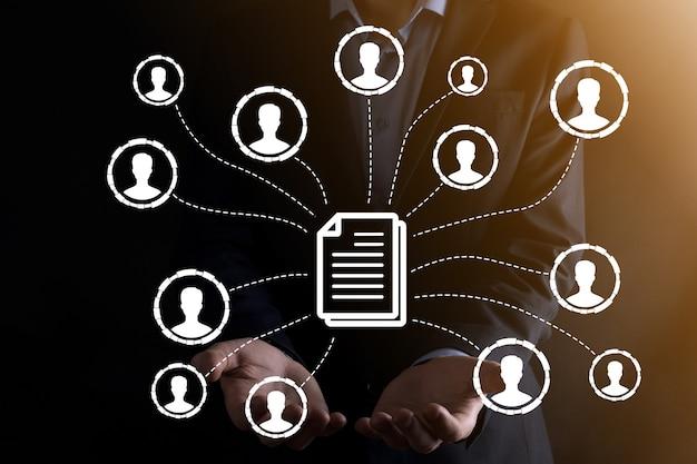L'homme tient l'icône du document et de l'utilisateur. système de gestion de données d'entreprise dms et concept de système de gestion de documents. un homme d'affaires clique ou publie sur un document lié aux utilisateurs de l'entreprise