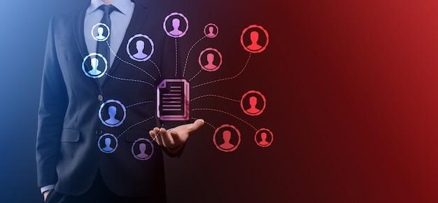 L'homme tient l'icône du document et de l'utilisateur. système de gestion de données d'entreprise dms et concept de système de gestion de documents. l'homme d'affaires clique ou publie sur un document lié aux utilisateurs de l'entreprise.