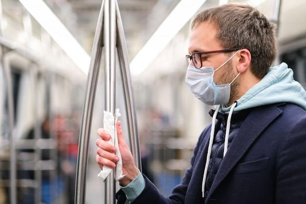 L'homme tient une main courante dans les transports en commun / métro à travers une serviette