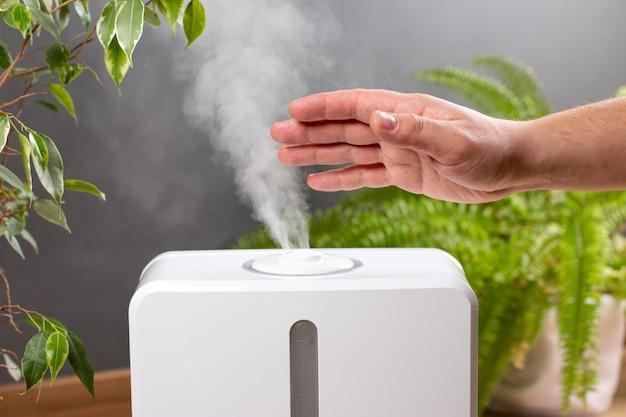 L'homme tient la main sur le diffuseur d'huile d'arôme de vapeur à la maison