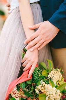 L'homme tient la main de la femme avec un bouquet de fleurs dans ses mains en gros plan