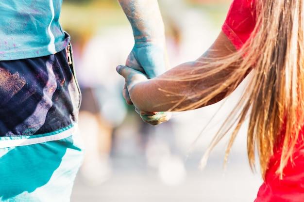 Un homme tient la main d'une femme pendant le festival des couleurs