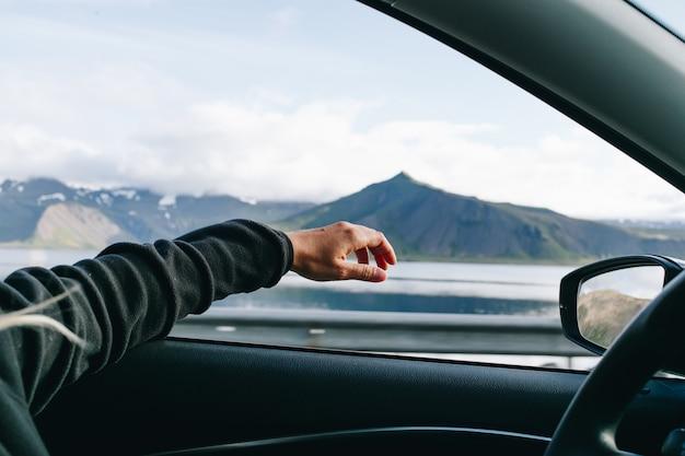L'homme tient la main lors de la conduite de voiture