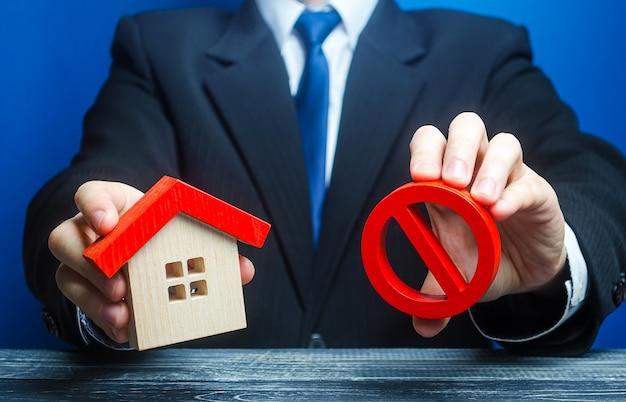 L'homme tient une maison et le symbole d'interdiction rouge non
