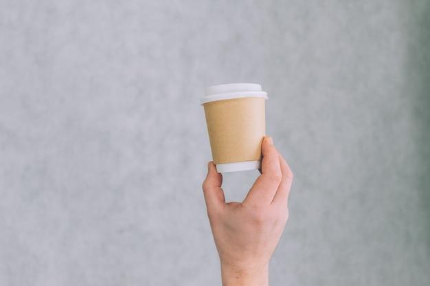 Un homme tient une maquette d'une tasse en papier pour le café et le thé sur une lumière.