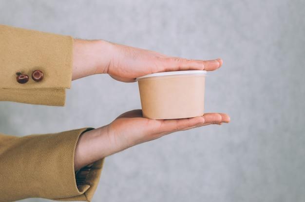 Un homme tient une maquette d'une tasse en papier pour la soupe, le café et le thé sur une lumière.