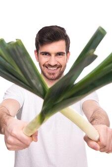 L'homme tient l'oignon vert dans ses mains et sourit.