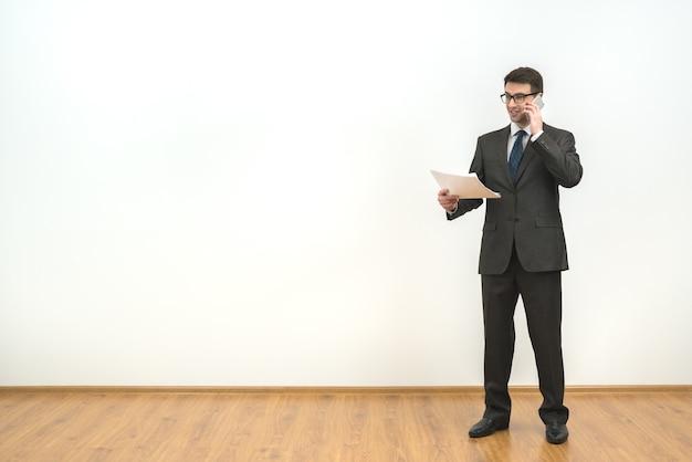 L'homme tient des papiers et des téléphones sur le fond du mur blanc