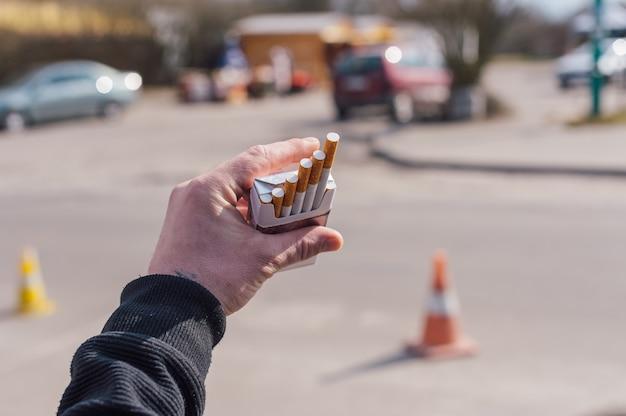 Un homme tient un paquet de cigarettes dans ses mains.