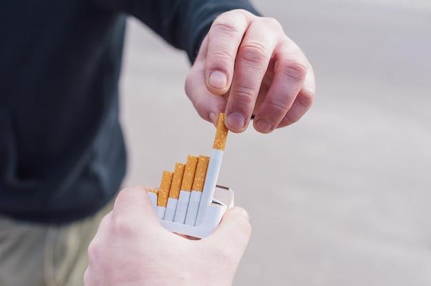 L'homme tient un paquet de cigarettes et le lui offre.