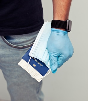 L'homme tient le passeport avec le billet de train et le masque médical à la main, portant les gants en latex comme une chose essentielle dans les voyages après le covid-19