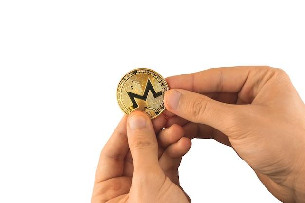 L'homme tient la pièce de monnaie de monero dans des mains d'isolement sur le fond blanc, photo de crypto-monnaie