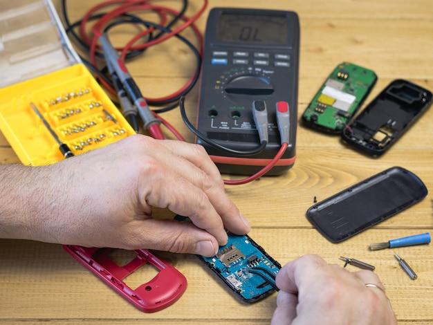 Un homme tient une pince à épiler d'un téléphone portable.