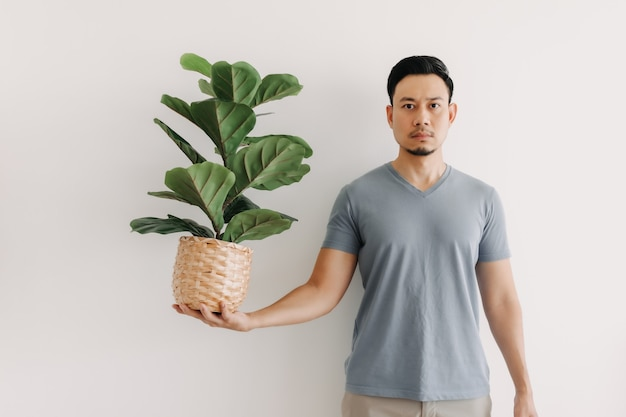 L'homme tient une plante d'intérieur isolée sur blanc