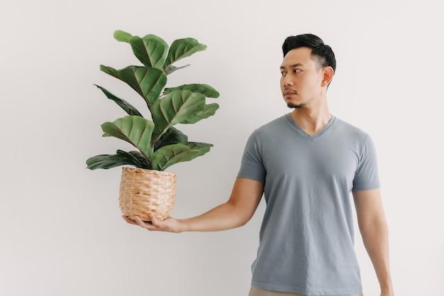 L'homme tient une plante d'intérieur isolée sur le concept blanc d'un amoureux des plantes