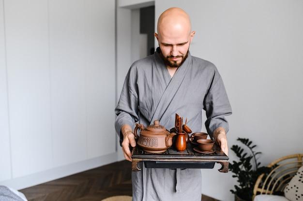 Un homme tient un plateau avec un ensemble pour une cérémonie du thé chinois.