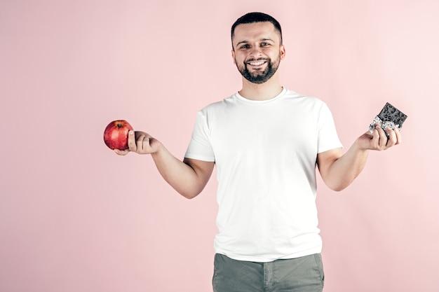 Un homme tient une pomme et du chocolat dans ses mains. nourriture saine et malsaine.