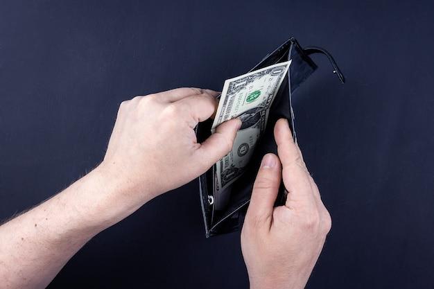 Un homme tient un portefeuille ouvert avec de l'argent dans ses mains.