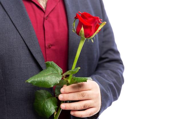 Un homme tient une rose rouge dans sa main. isolé sur mur blanc. fermer.