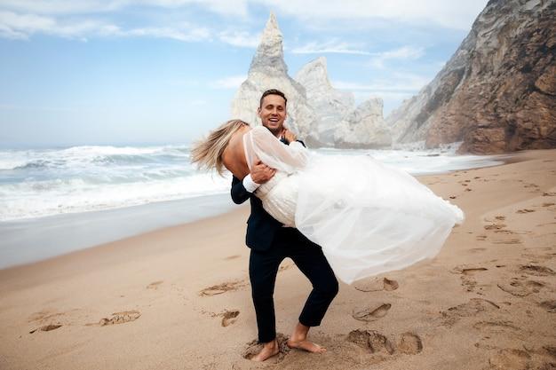 L'homme tient sa femme sur les mains et ils ont l'air très heureux
