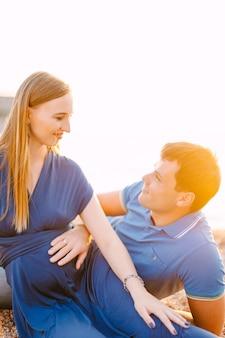 L'homme tient sa main sur le ventre d'une femme enceinte souriante dans une longue robe bleue