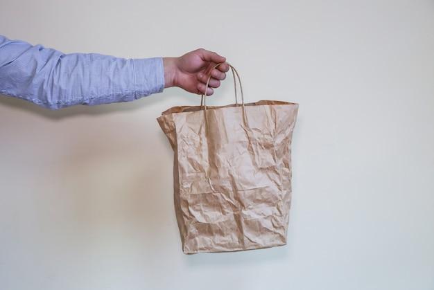 L'homme tient un sac écologique en papier kraft.
