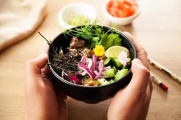 Un homme tient une salade poke avec du boeuf dans un bol dans ses mains ingrédients boeuf nameko champignons cerise