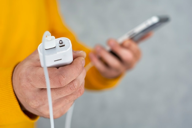 L'homme tient un smartphone et un chargeur portable dans ses mains sur fond gris. power bank charge le téléphone.